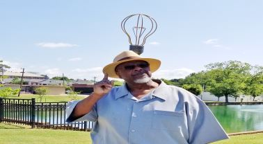 Robert Malone poses in front of the light bulb sculpture