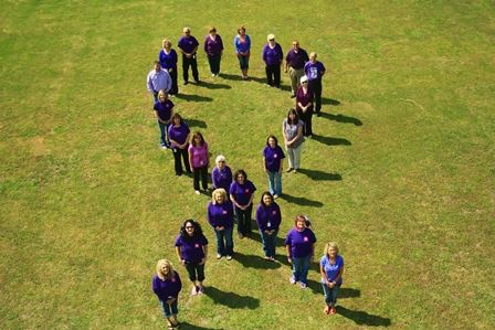 Aerial view of people forming a ribbon shape in a field
